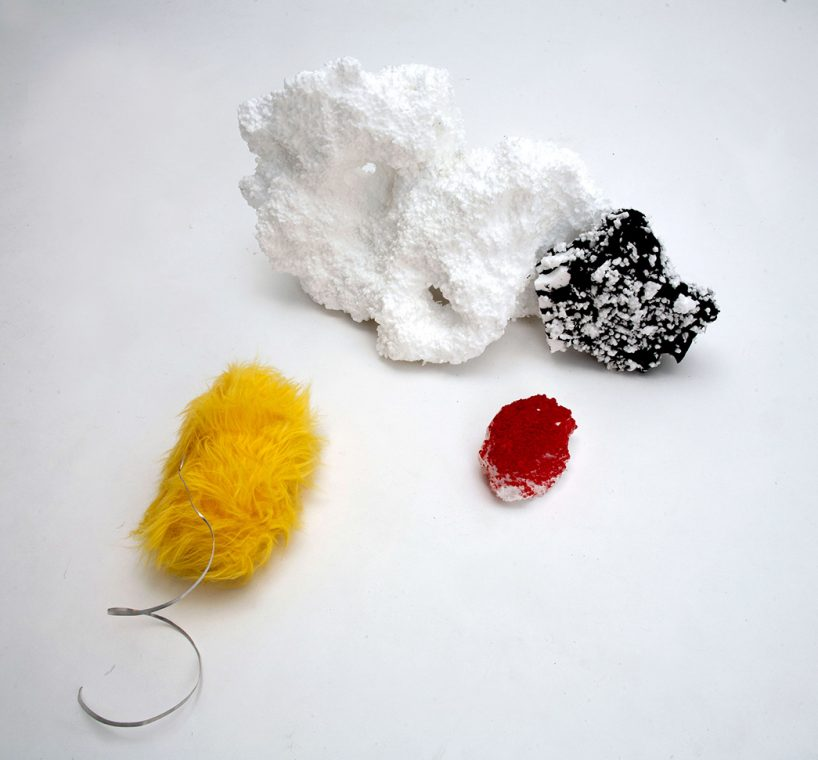 mixed media composition with white and black styrofoam, metal curl, and yellow fur