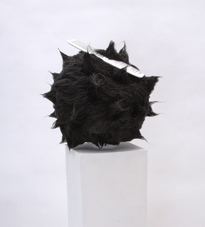 black spike fur sculpture with comb on white pedestal