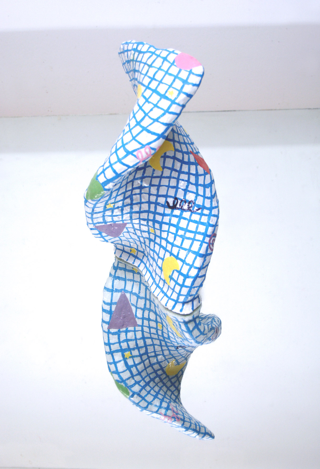 a white curled hydrocal sculpture with a blue grid and simple colored shapes on a mirror