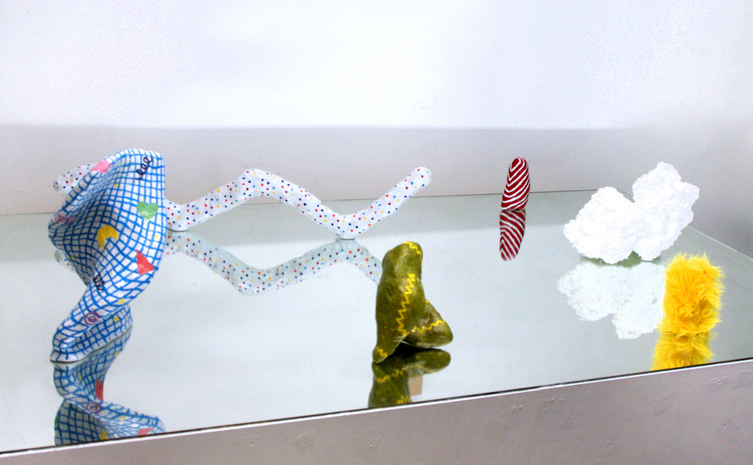 A group of 4 hydrocal sculptures, one styrofoam sculpture, and one yellow fur sculpture all on a mirror pedestal