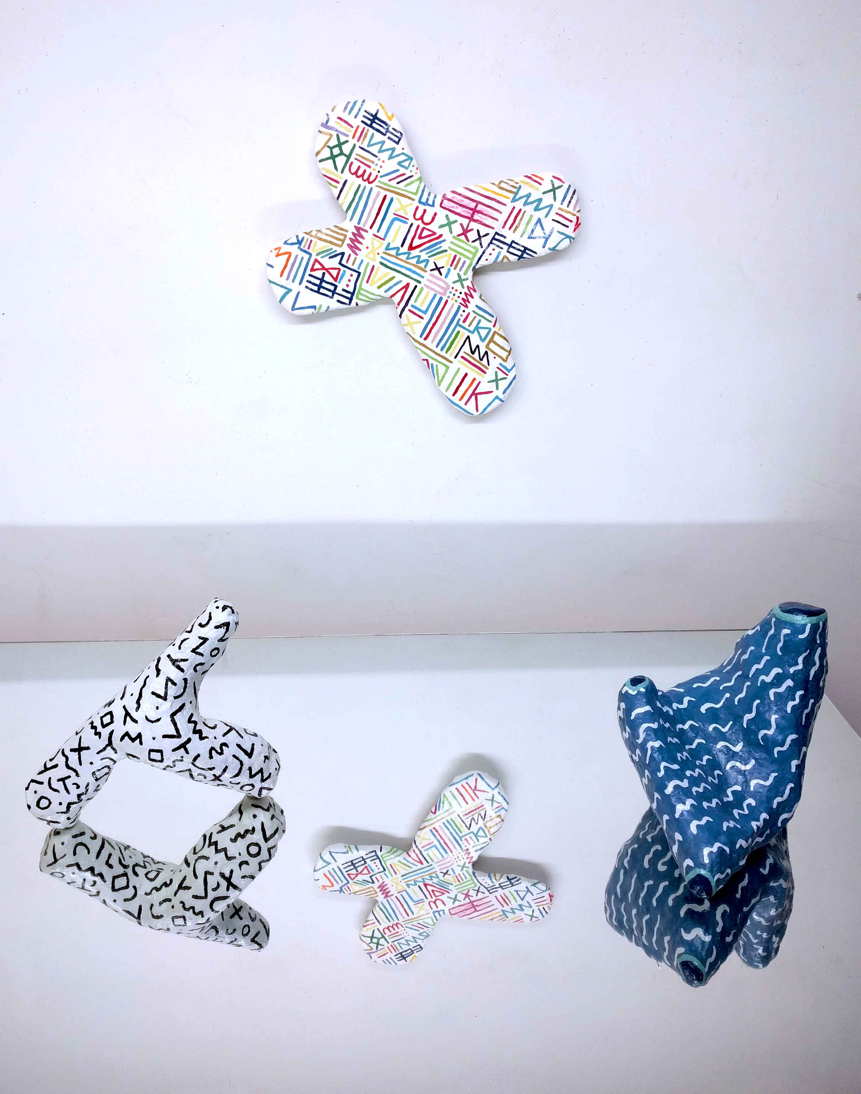 A group of three hydrocal sculptures with thin lines. Two are on a mirror and one is on the wall behind them.