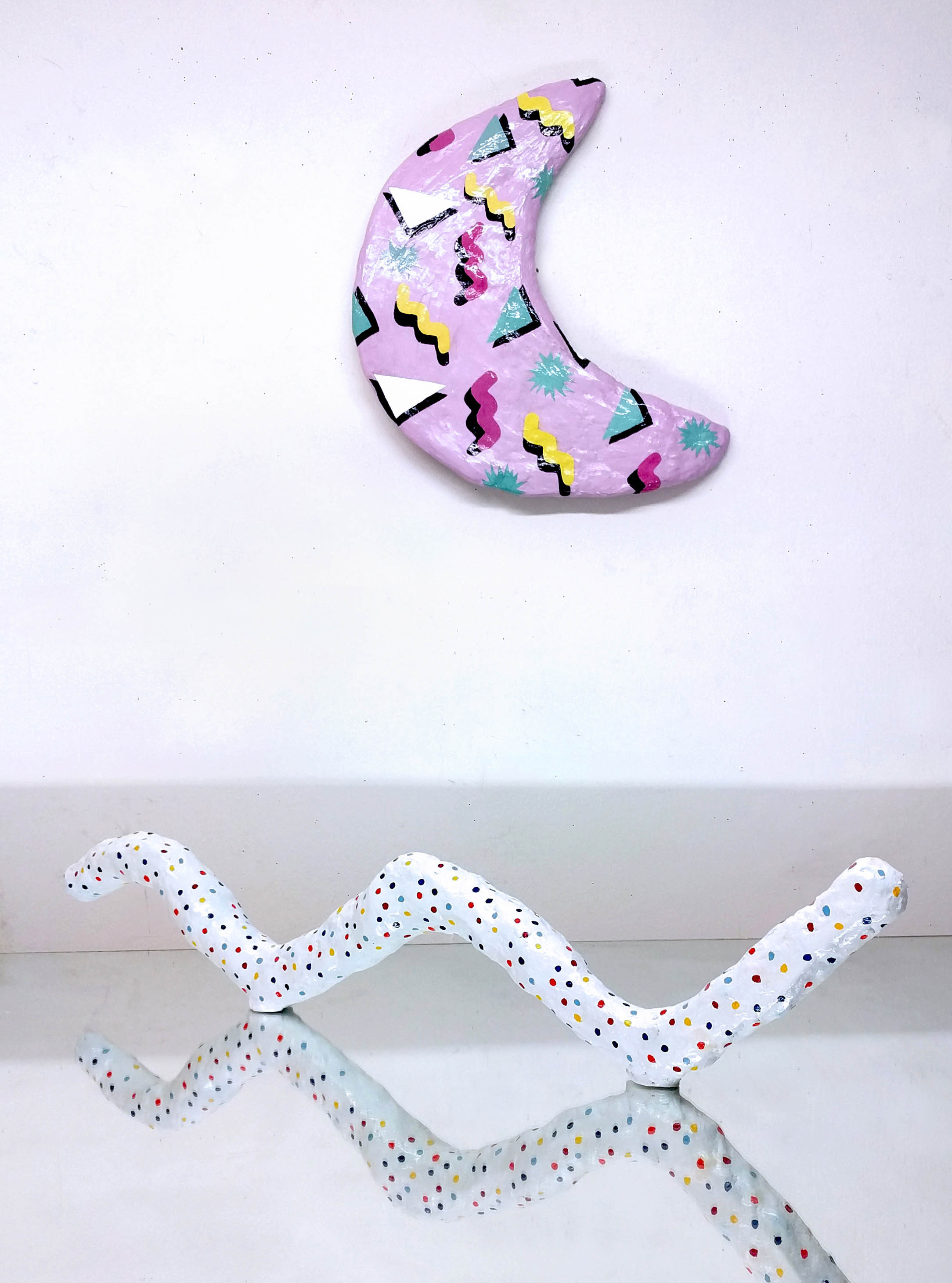 A pink 80s style hydrocal moon sculpture and a white, thin wormlike wavy hydrocal sculpture on a mirror