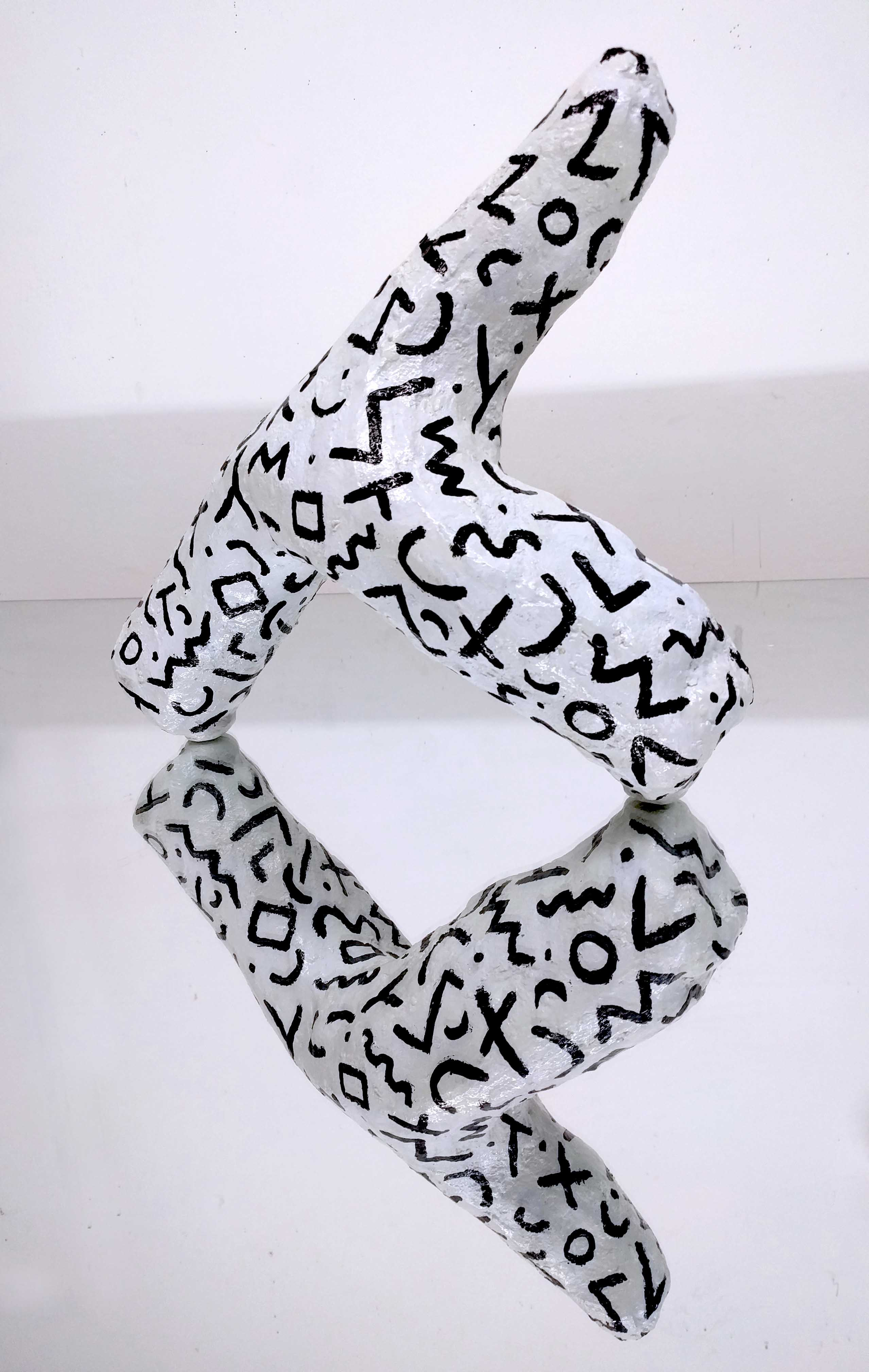 white hydrocal y shape with variety black curled line pattern on a mirror