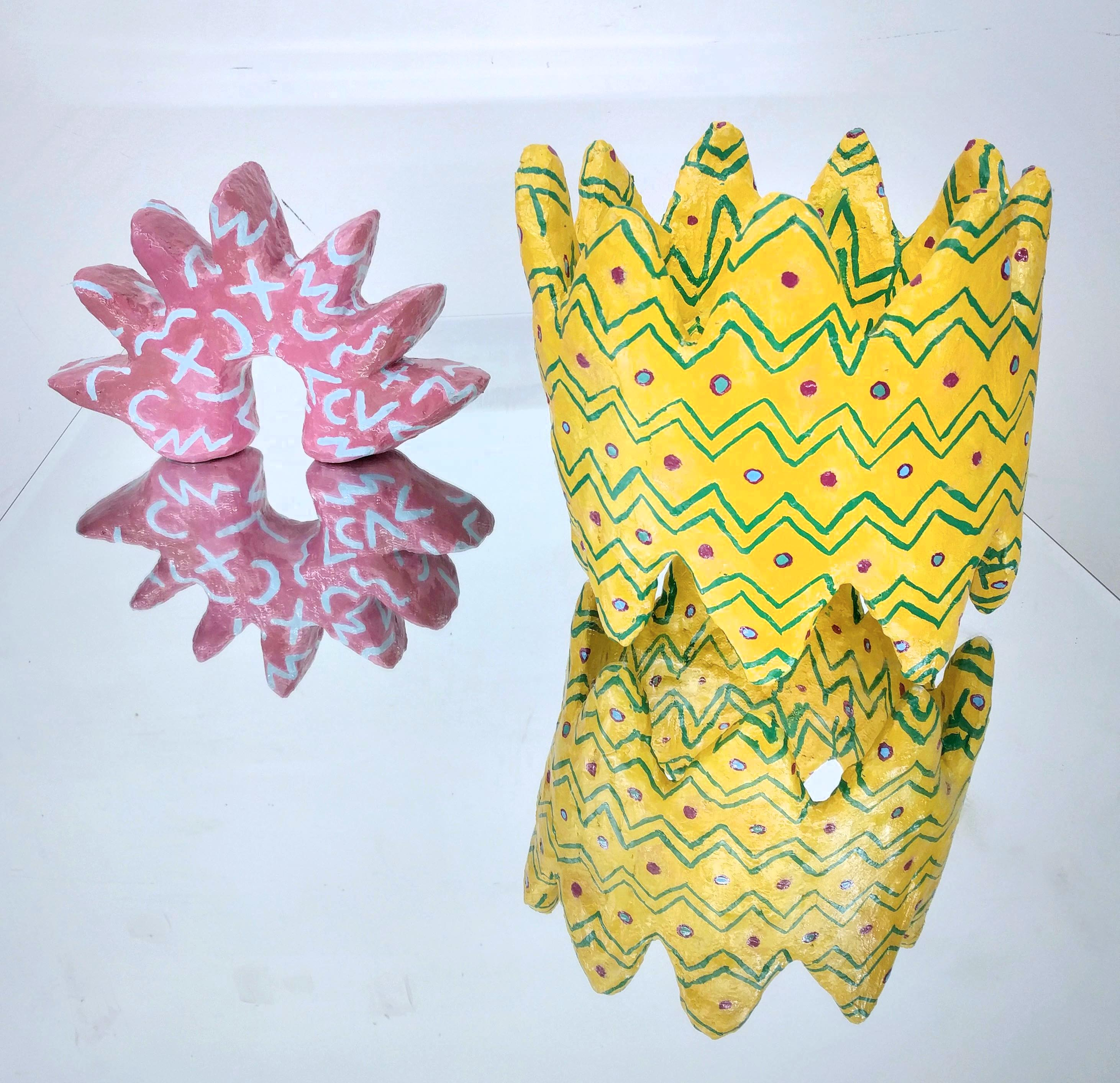 a spikey pink sculpture and yellow crown sculpture hydrocal