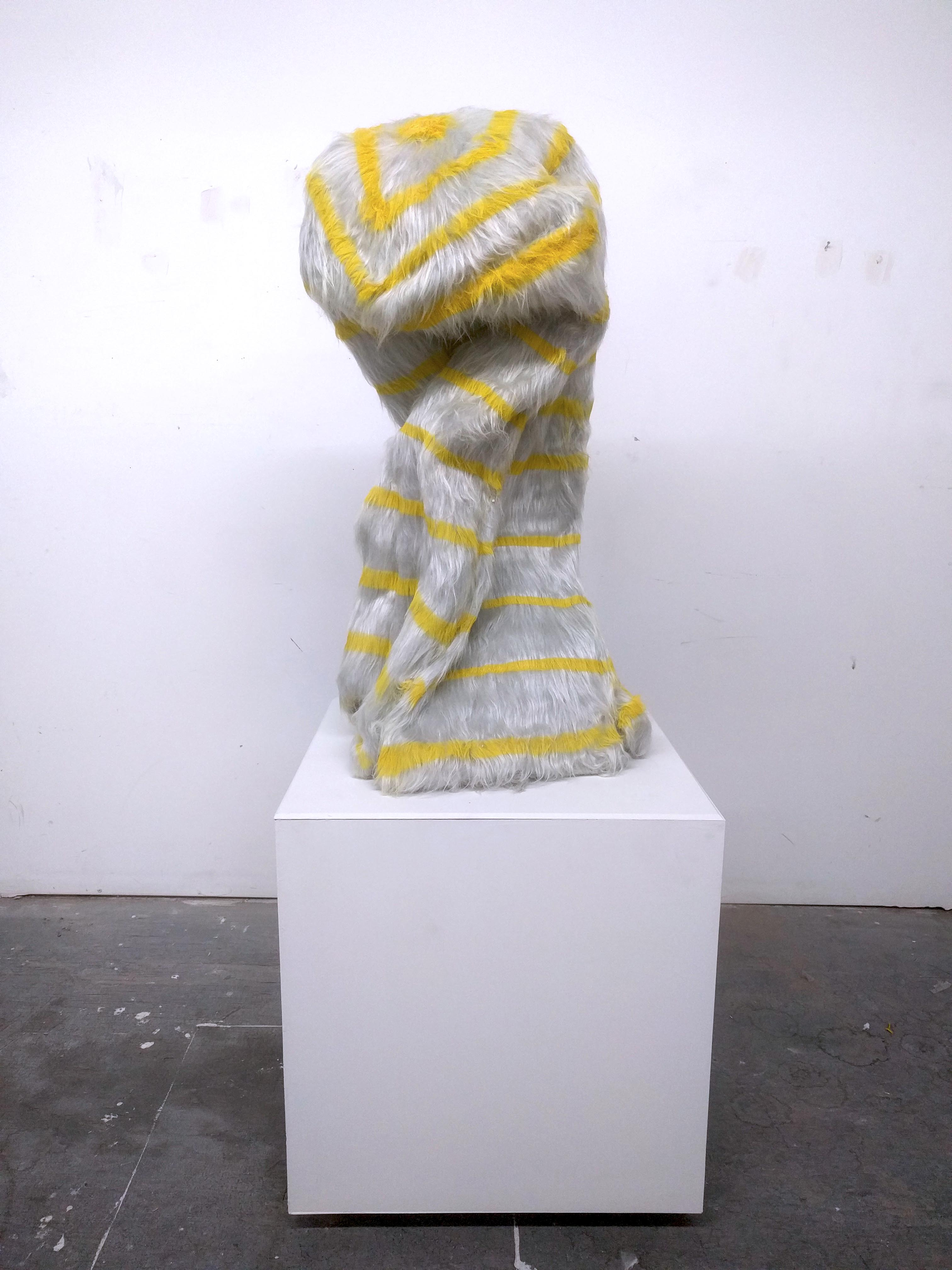 a gray fur figure with yellow stripes crushed in on itself