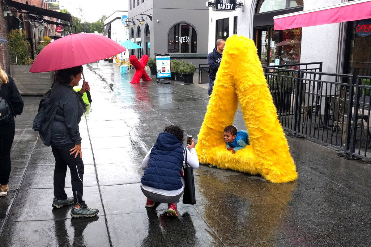 a boy posing on a yellow triangle fur sculpture and someone taking his picture