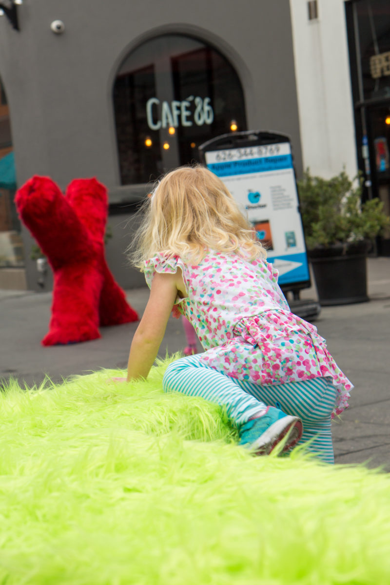 a girl playing on a green fur bench