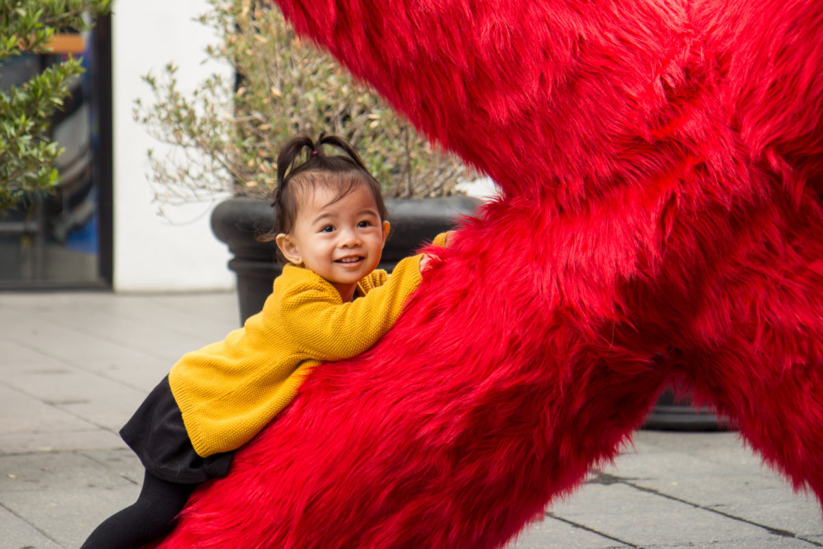 a little girl laying on a red fur x sculpture looking at camera