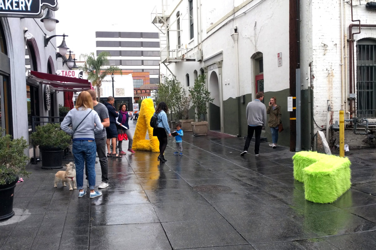 a group of people around two fur sculptures