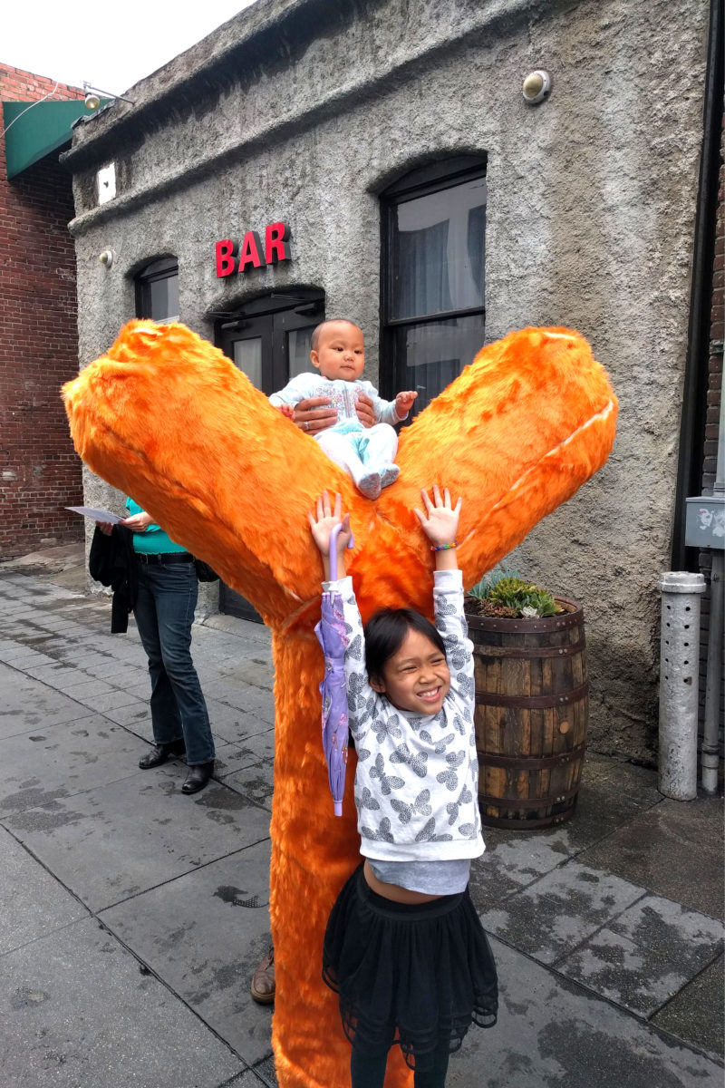 a girl posing and a baby sitting on top of an orange y shaped fur sculpture