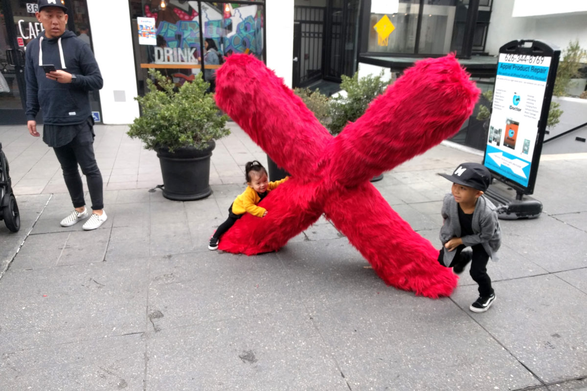 a boy and girl playing around a large x shaped fur sculpture