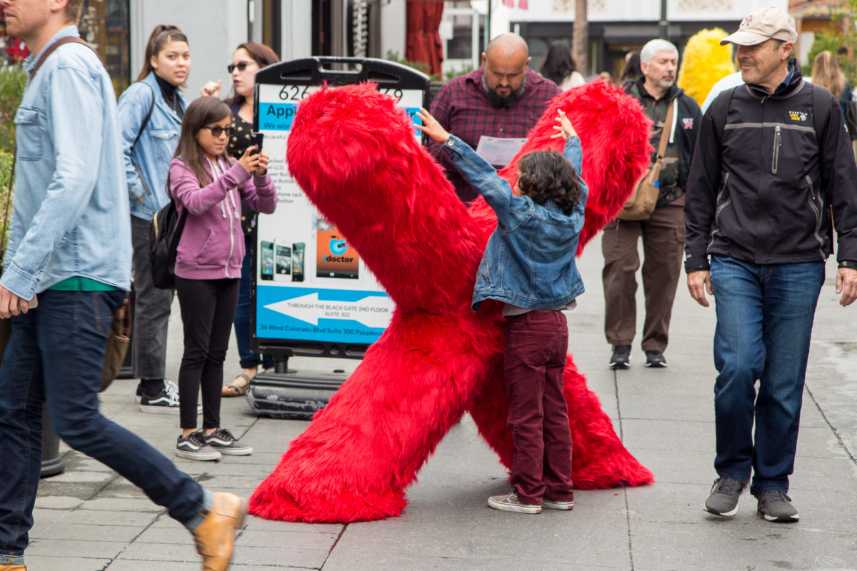 a boy posing around a large x fur sculpture