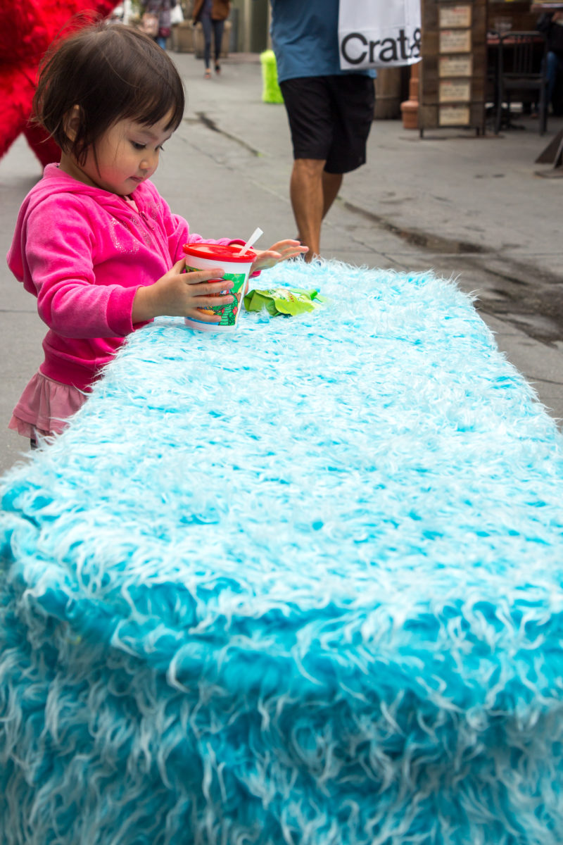 a little girl playing on a blue fur bench sculpture