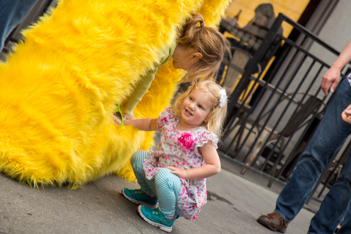 a little girl petting a yellow fur sculpture