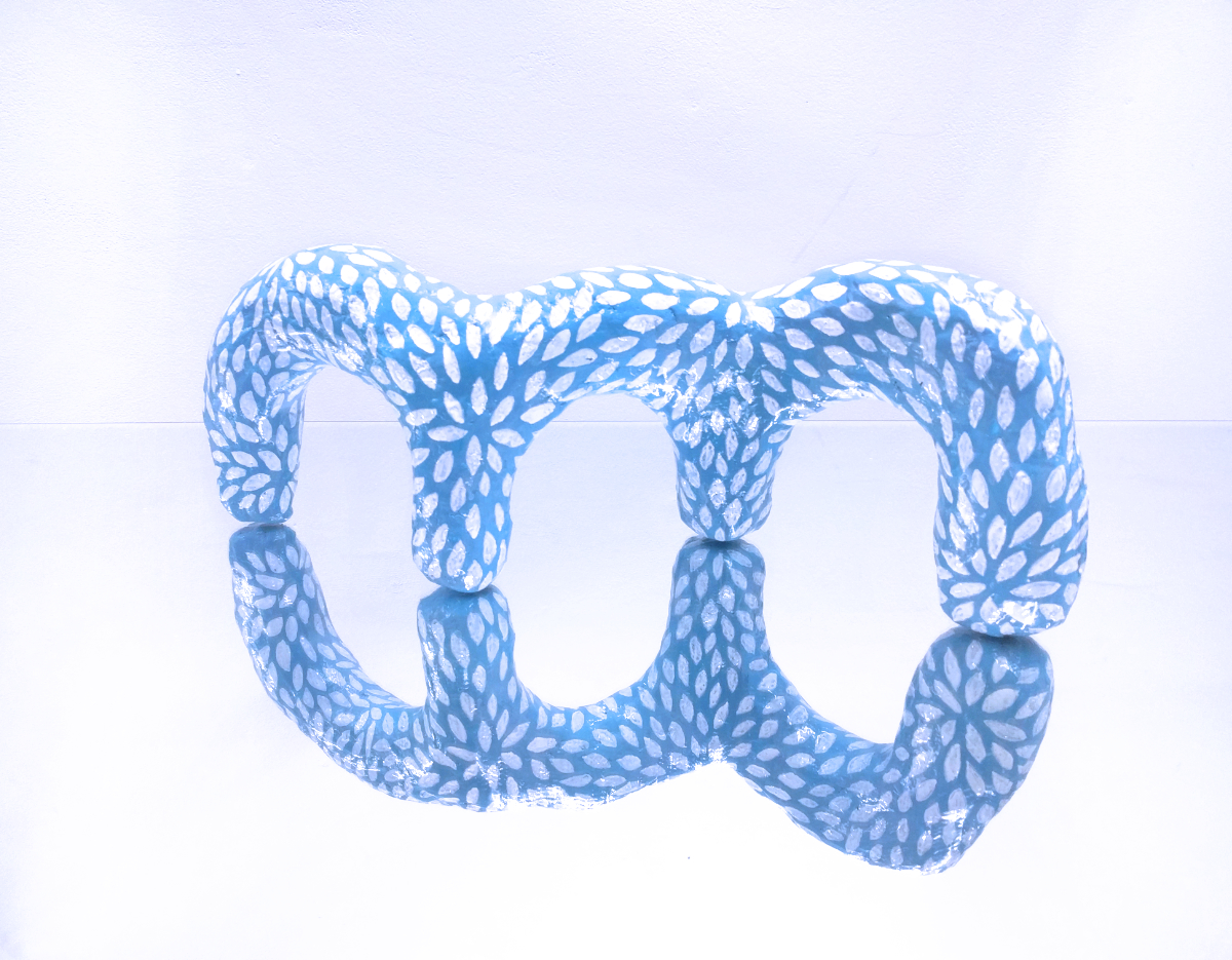 white seed pattern hydrocal sculpture containing three blue arches sitting on a mirror